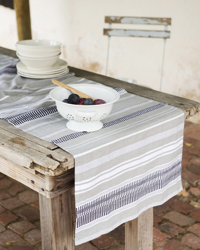 The Mungo Linen Lisburn Table Runner in Rolled Grey set at an el fresco country table.