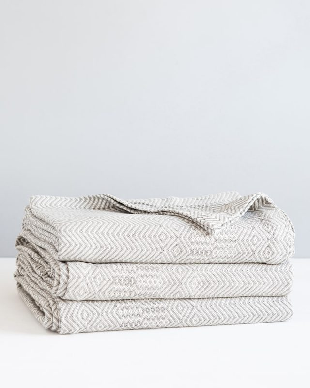 Stack of Mungo Cotton Bakuba Throws in Smoke. Textile woven with all natural fibres at our mill in Plettenberg Bay, South Africa.